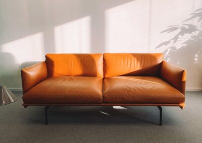 2-seat-orange-leather-sofa-beside-wall-1866149